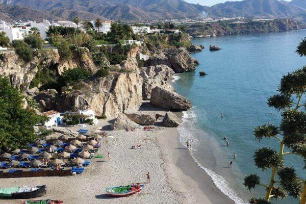 solservice - en strand med solstolar med klippig bakgrund